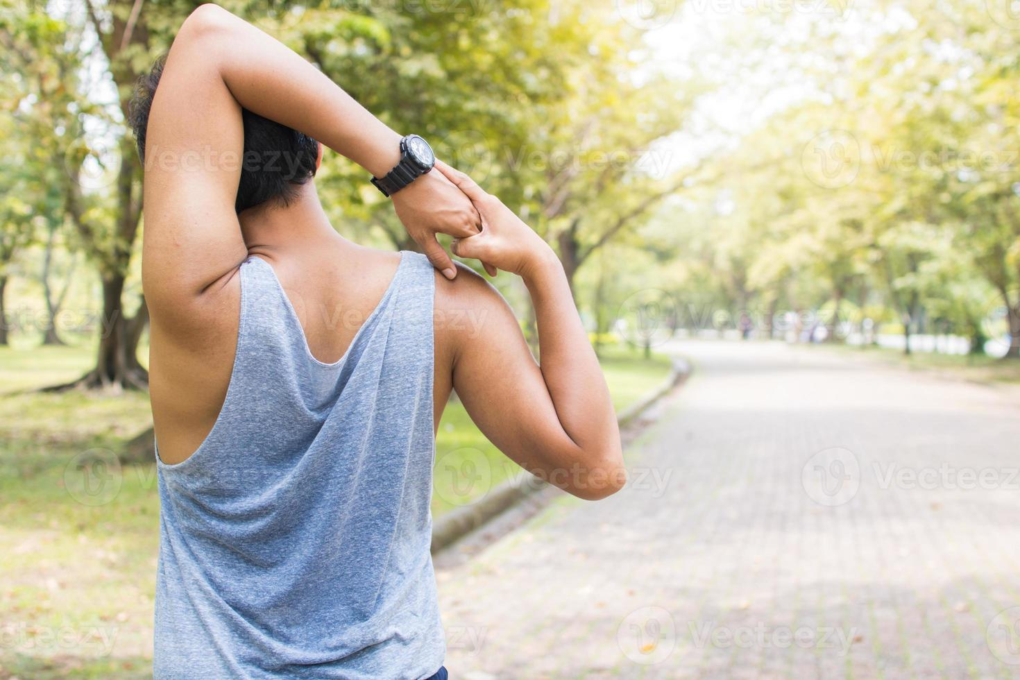 Hombre haciendo estiramientos de brazos en un parque foto