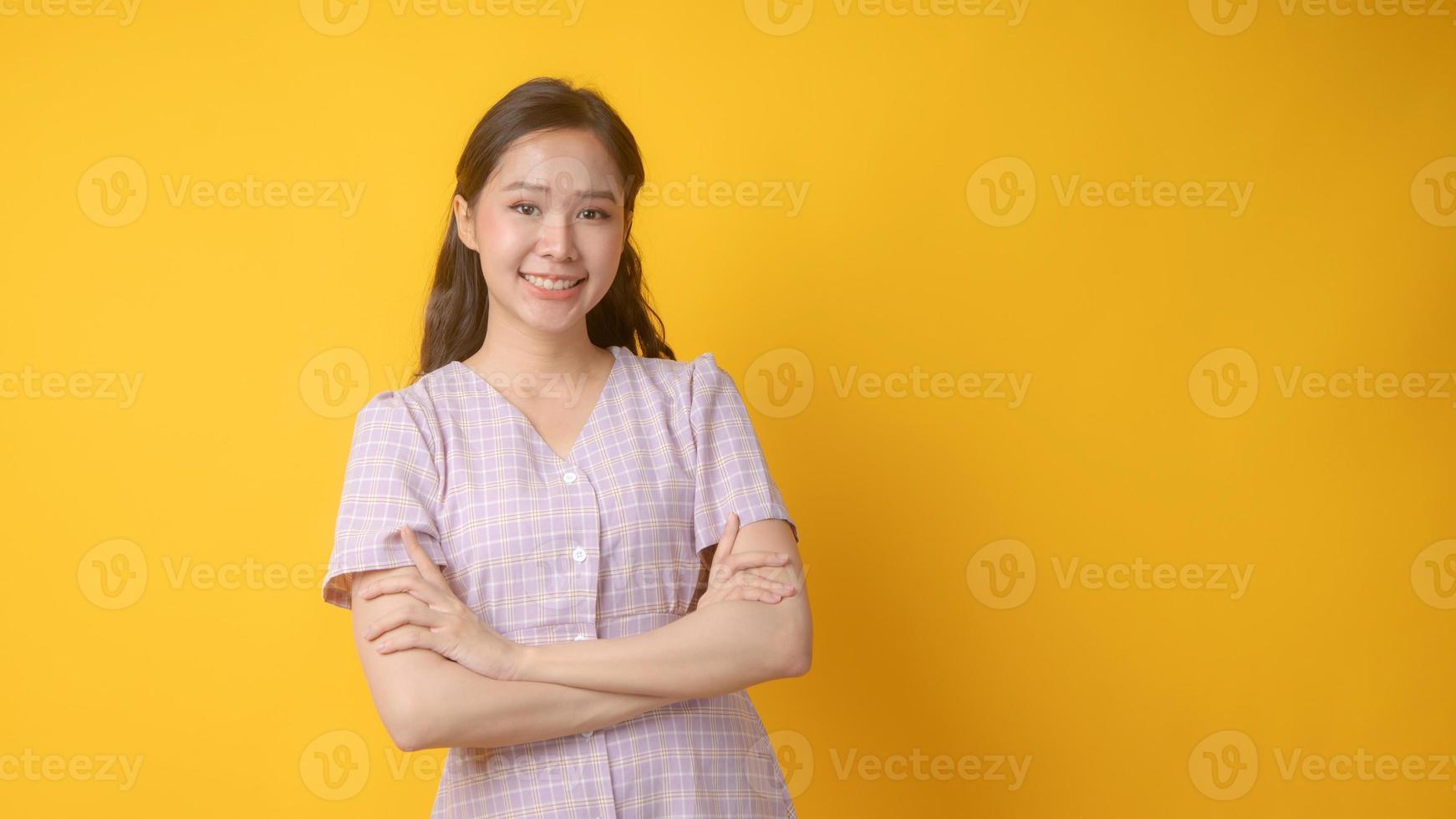 Mujer asiática sonriendo con los brazos cruzados y mirando a la cámara sobre fondo amarillo foto