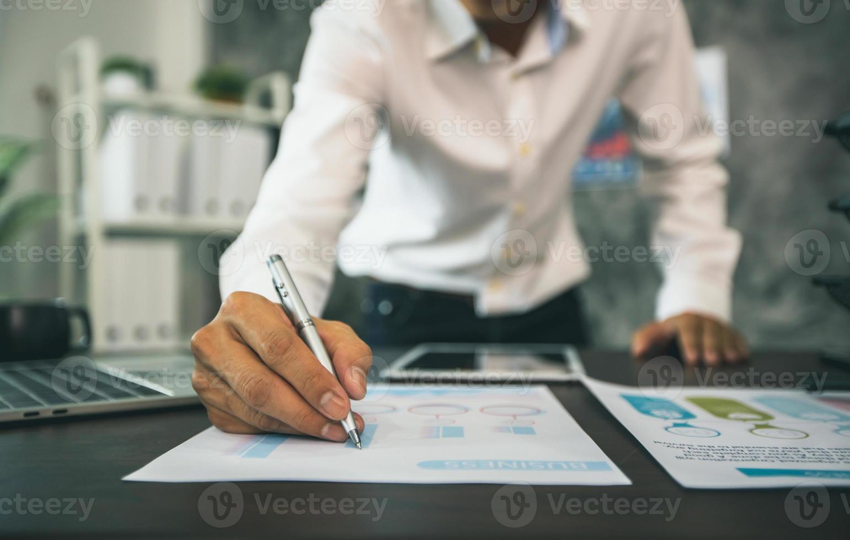 Close-up de empresario escribiendo en papeles de tablas y gráficos junto a la tableta y el portátil foto