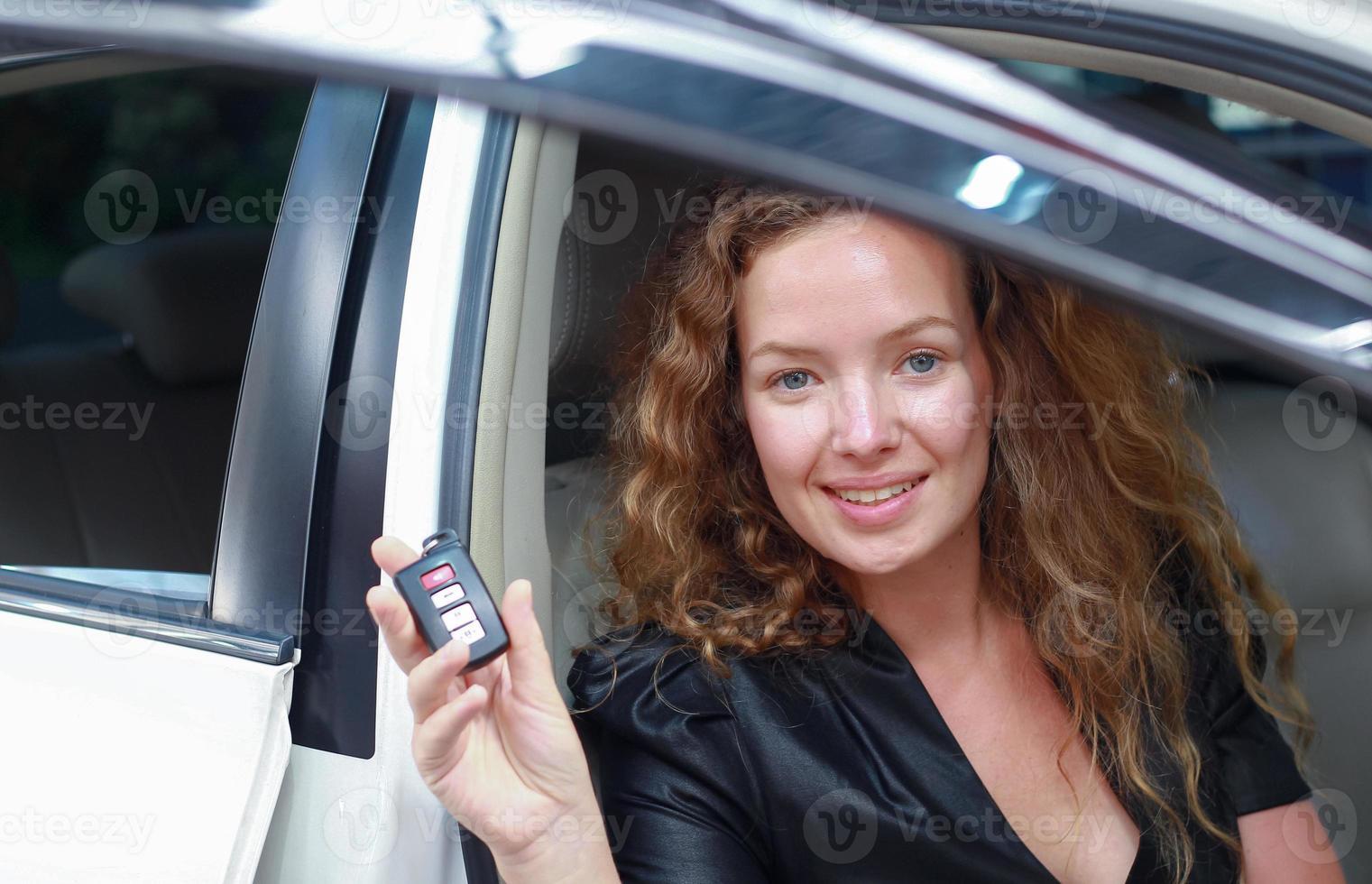 hermosa mujer sonríe feliz con la compra de un auto nuevo en la sala de exposición foto