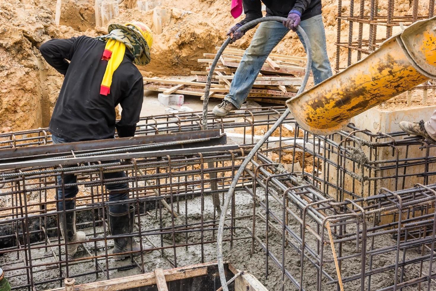 Vertido de hormigón durante el hormigonado comercial de suelos de edificios en obra foto