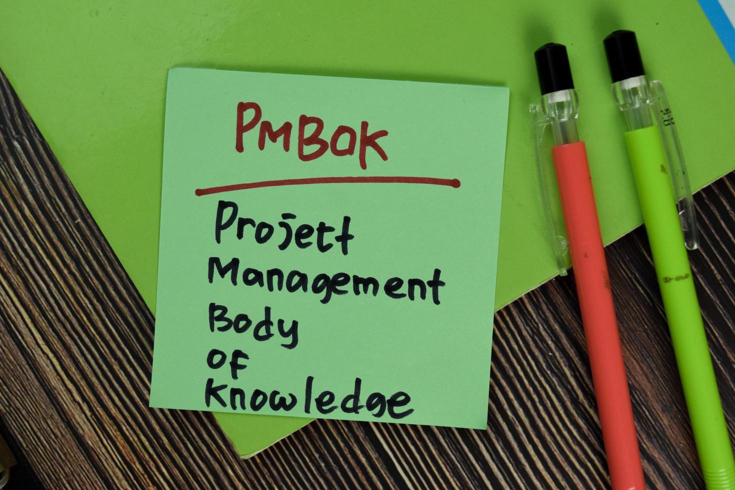 pmbok - cuerpo de conocimientos de gestión de proyectos escrito en una nota adhesiva aislado en la mesa de madera foto