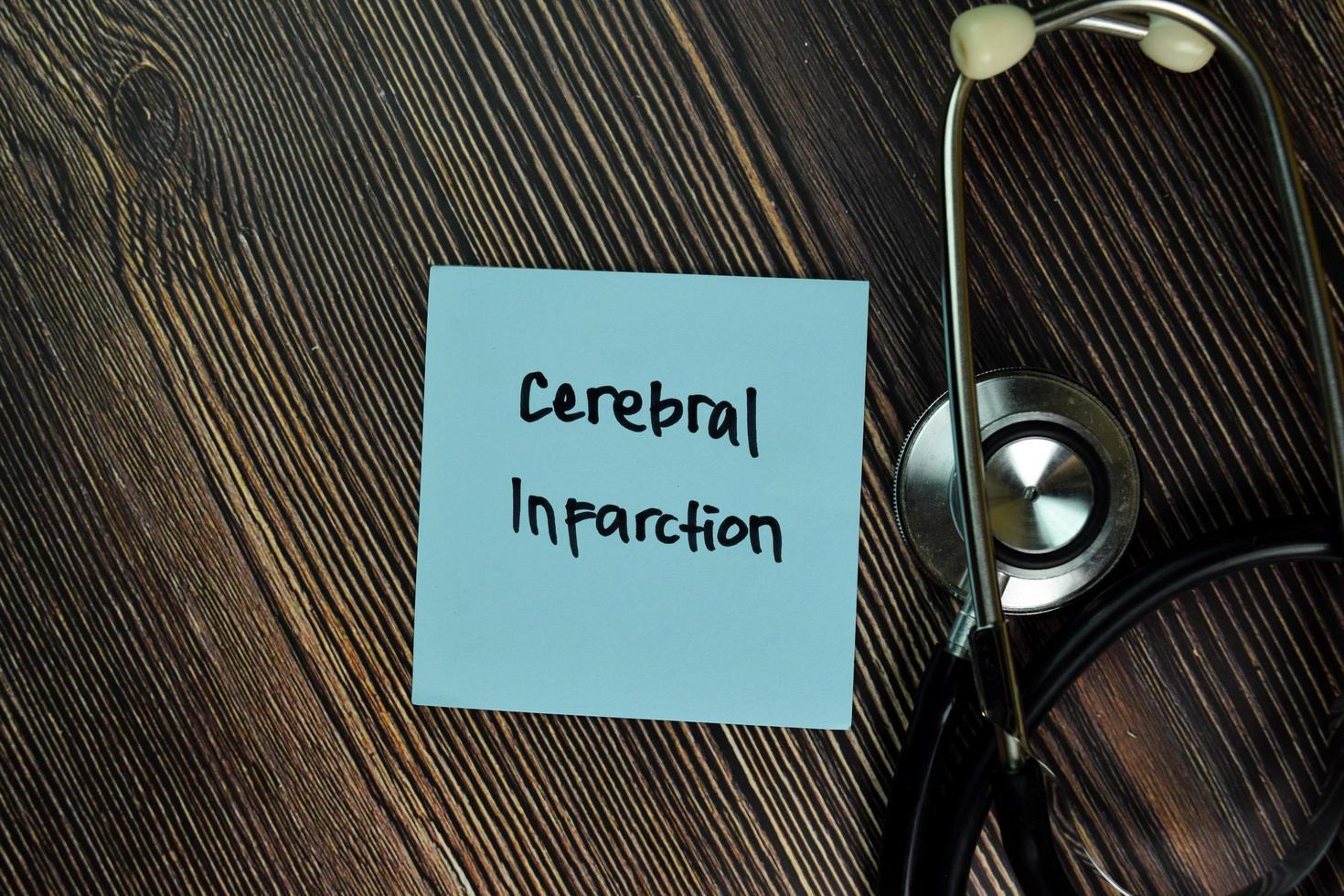 Infarto cerebral escrito en una nota adhesiva aislado en la mesa de madera foto