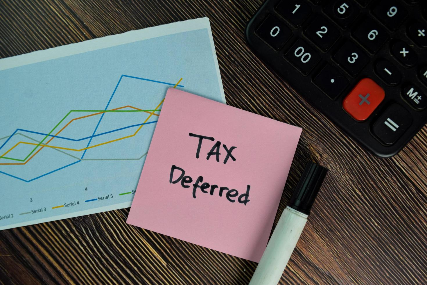 Impuestos diferidos escrito en nota adhesiva aislado sobre mesa de madera foto