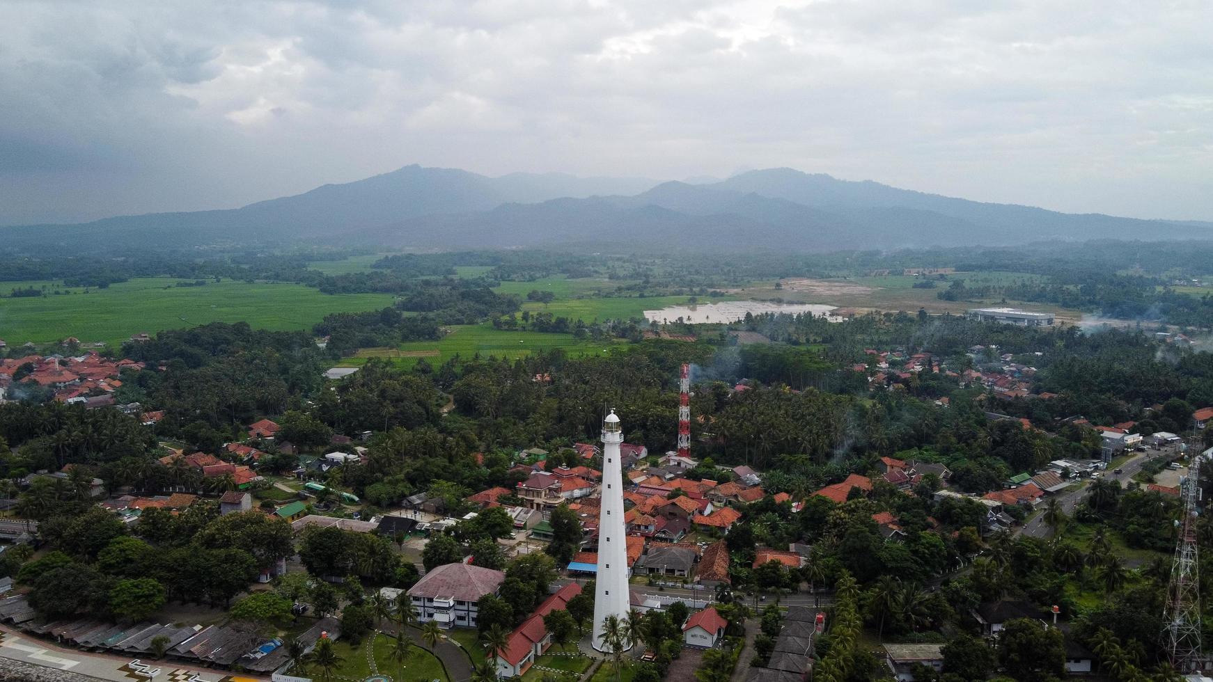 banten, indonesia 2021 - vista aérea del paisaje de la puesta del sol de la roca del mar del faro foto