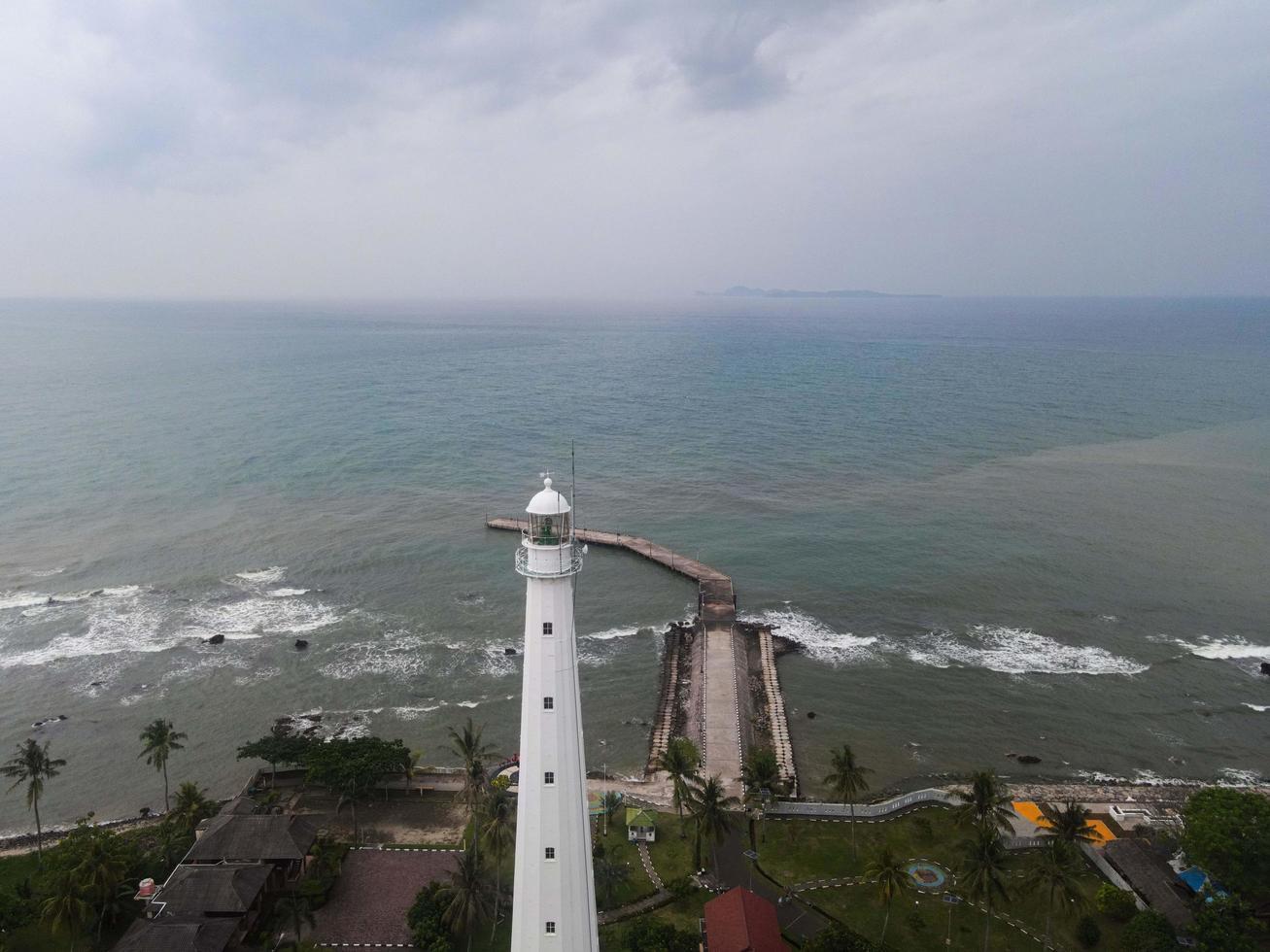 Banten, Indonesia 2021: vista aérea del paisaje al atardecer de la roca del mar del faro foto