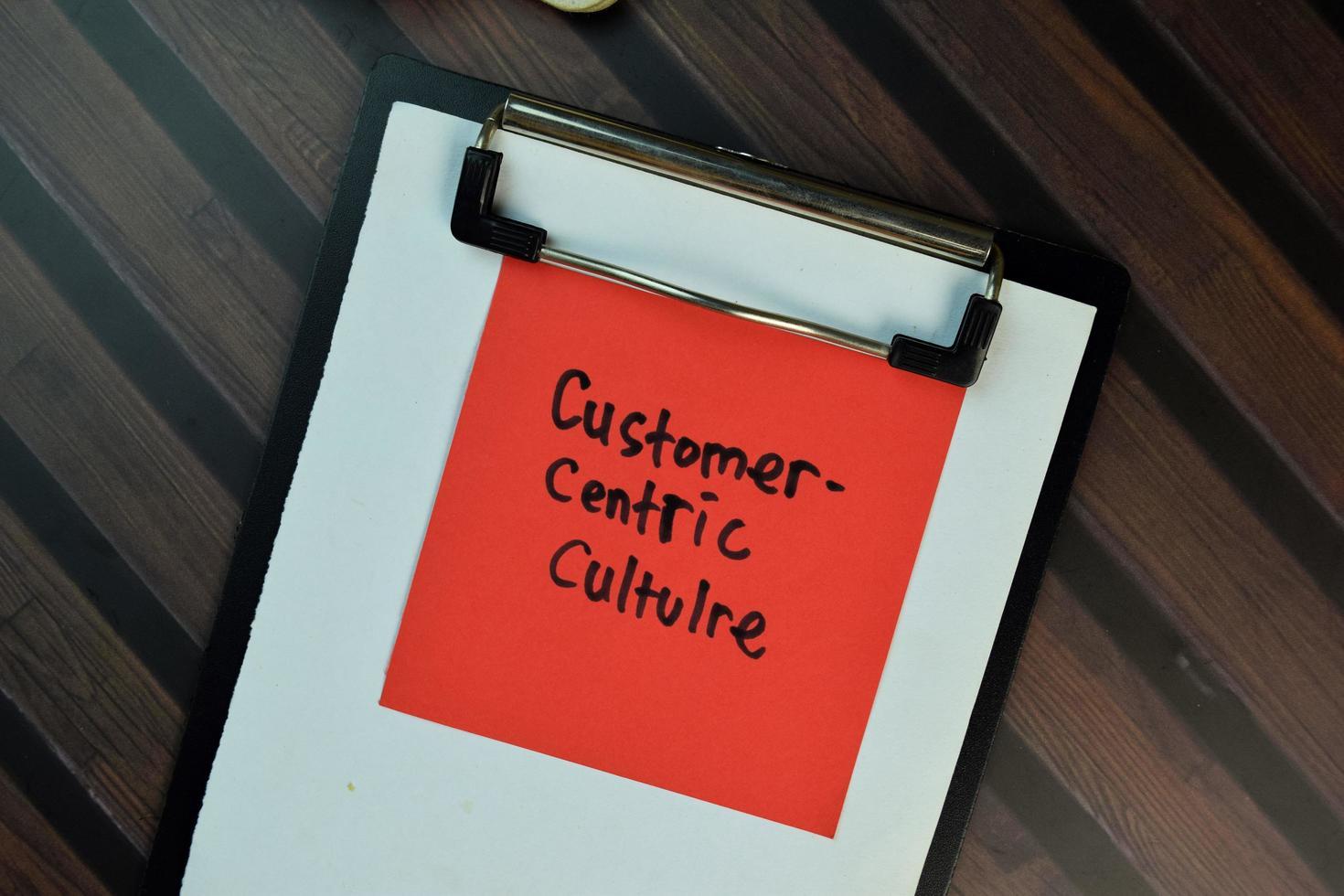 Cultura centrada en el cliente escrito en una nota adhesiva aislado en la mesa de madera foto