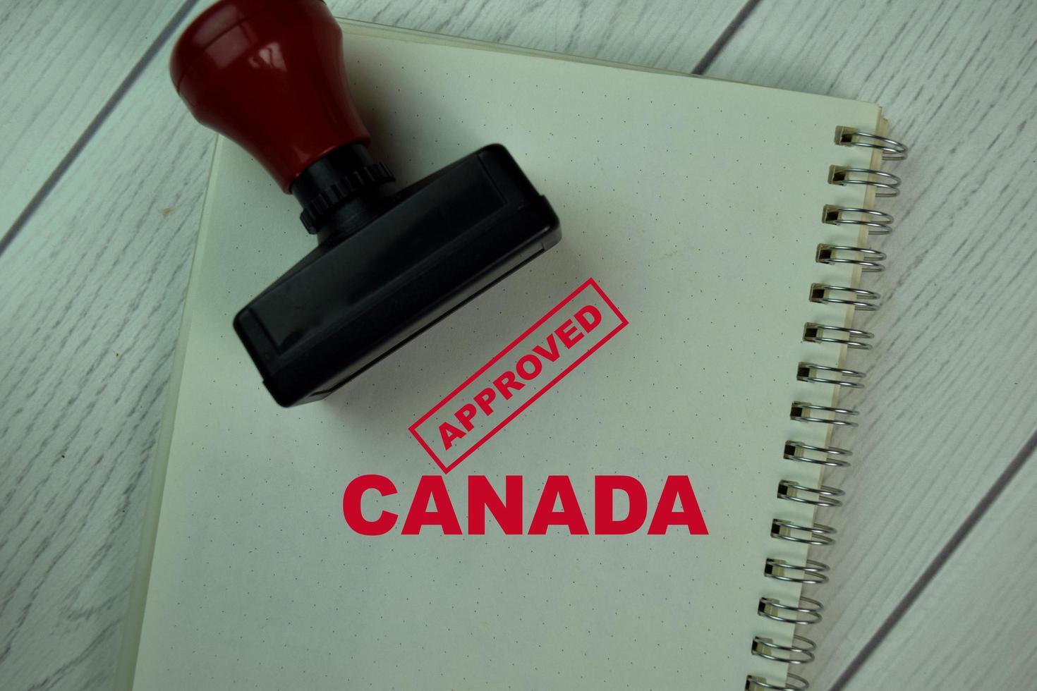 Sello de goma con mango rojo y texto aprobado de Canadá aislado en la tabla foto