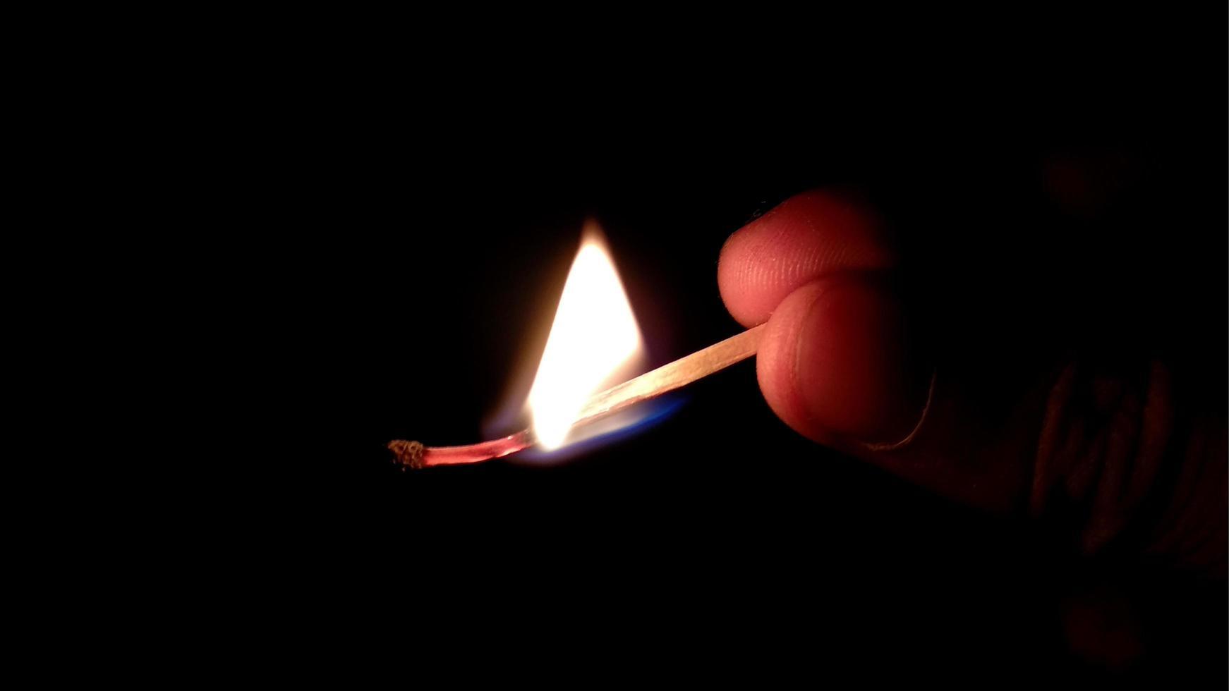 Fósforo con la llama y el humo ardiendo, aislado en un fondo negro foto