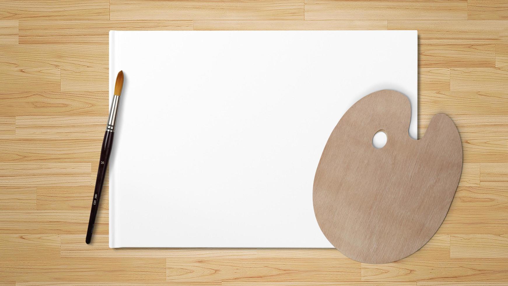Nueva paleta de madera con pincel de arte, aislado sobre fondo blanco y fondo de madera foto