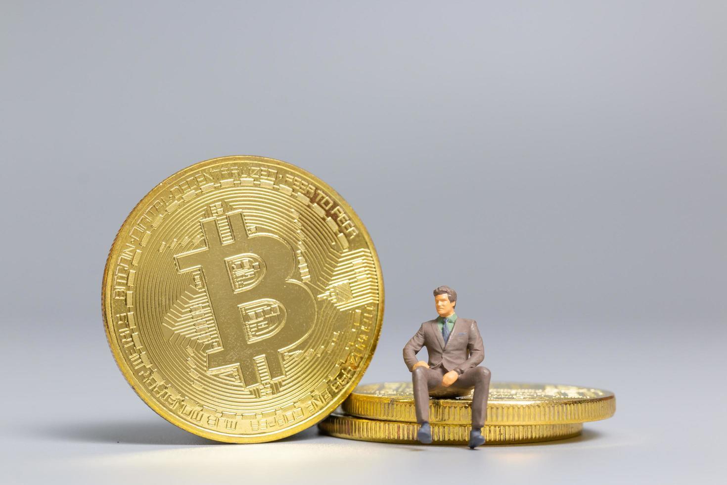 Empresario en miniatura sentado en monedas bitcoin, concepto de inversión futura foto