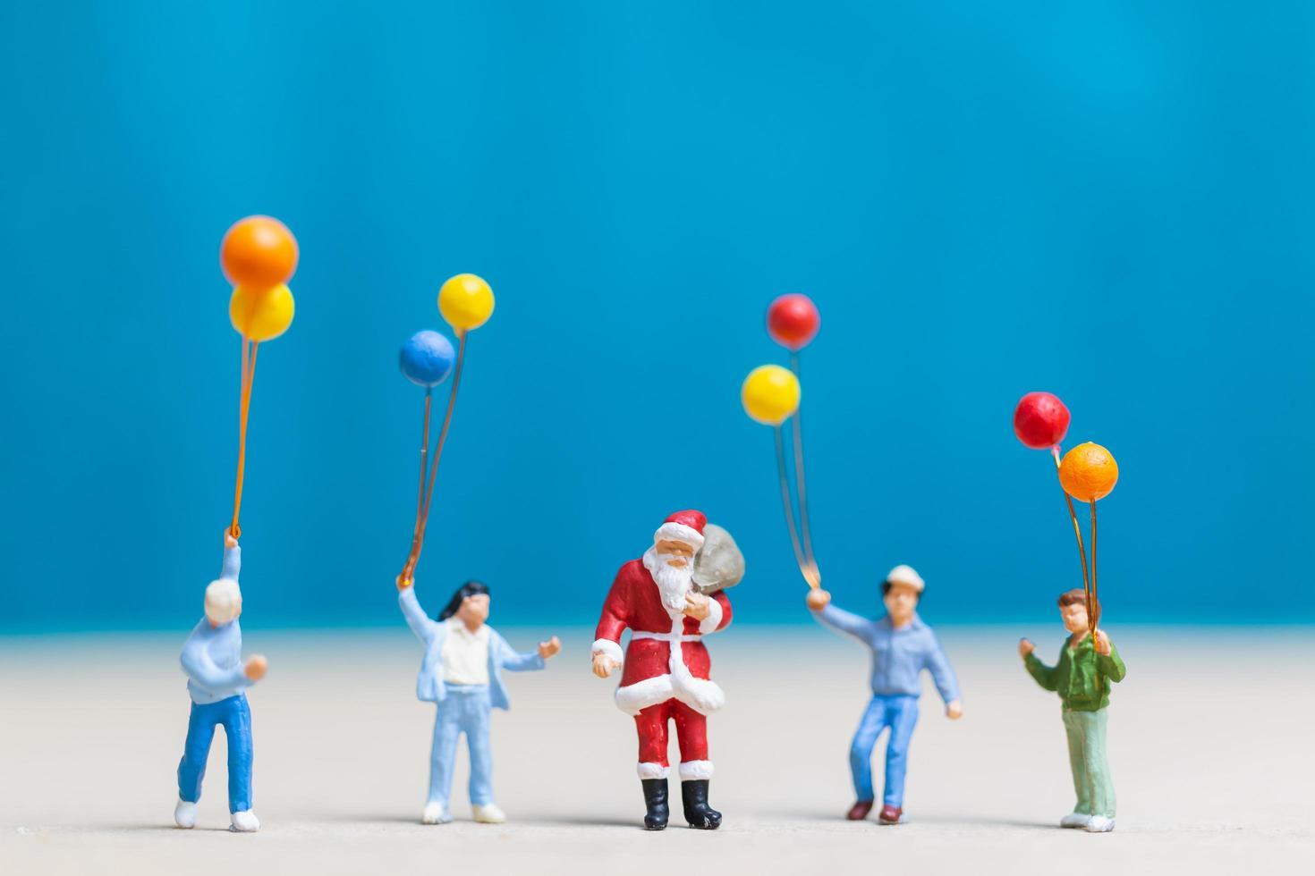 Papá Noel en miniatura y niños sosteniendo globos, feliz navidad y feliz año nuevo concepto foto