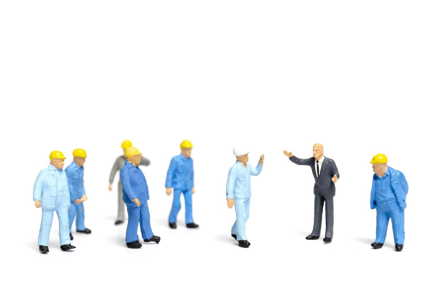Gente en miniatura escuchando a un político hablando durante un mitin electoral foto