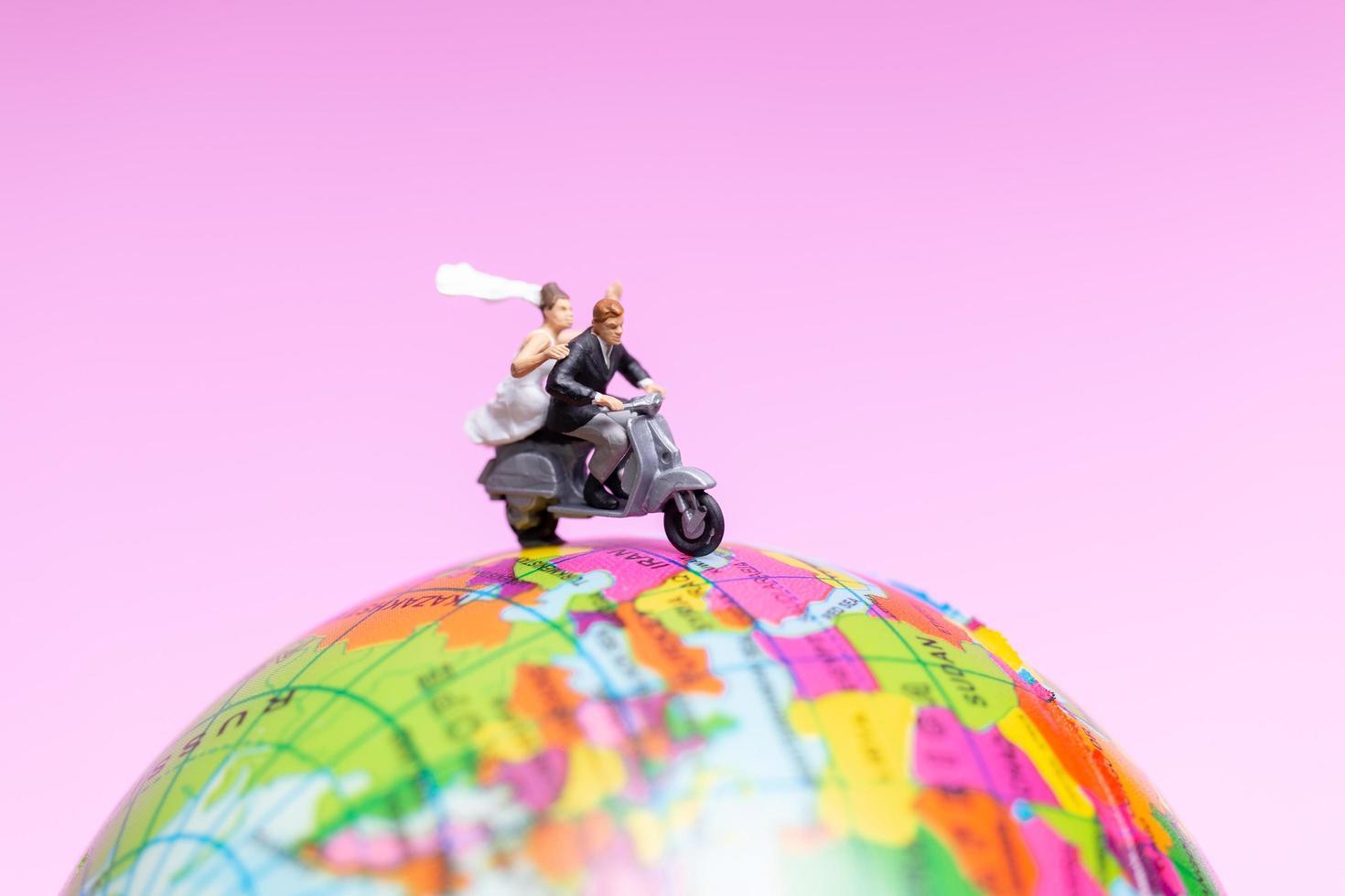 Pareja en miniatura en motocicleta en un globo terráqueo foto