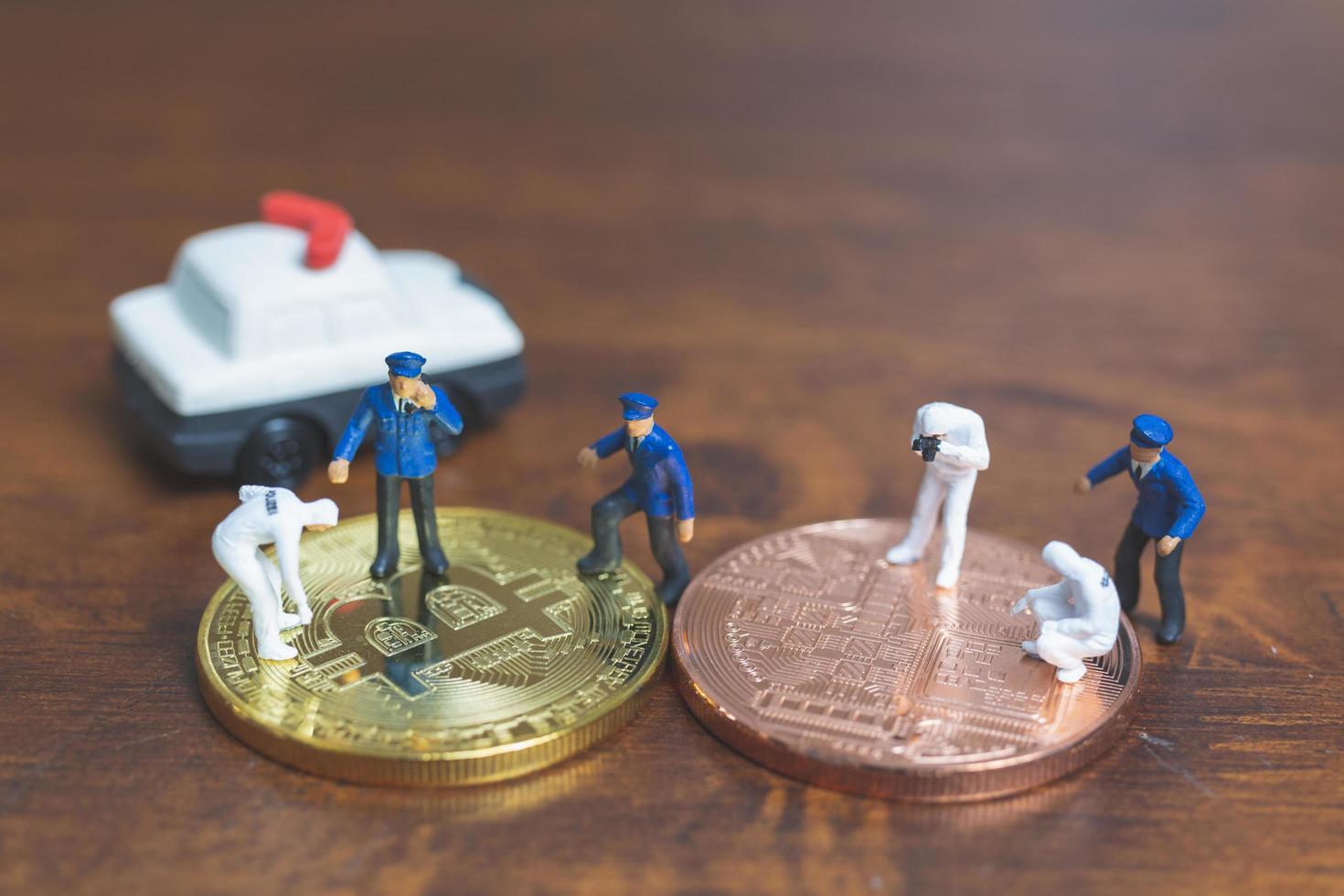 Policía y detectives en miniatura de pie delante de la criptomoneda bitcoin, concepto de ciberdelincuencia foto