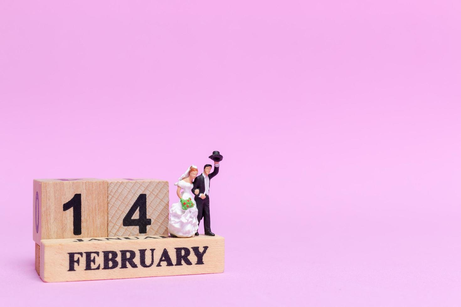 Novios en miniatura sobre un fondo rosa, el día de San Valentín y el concepto de boda foto