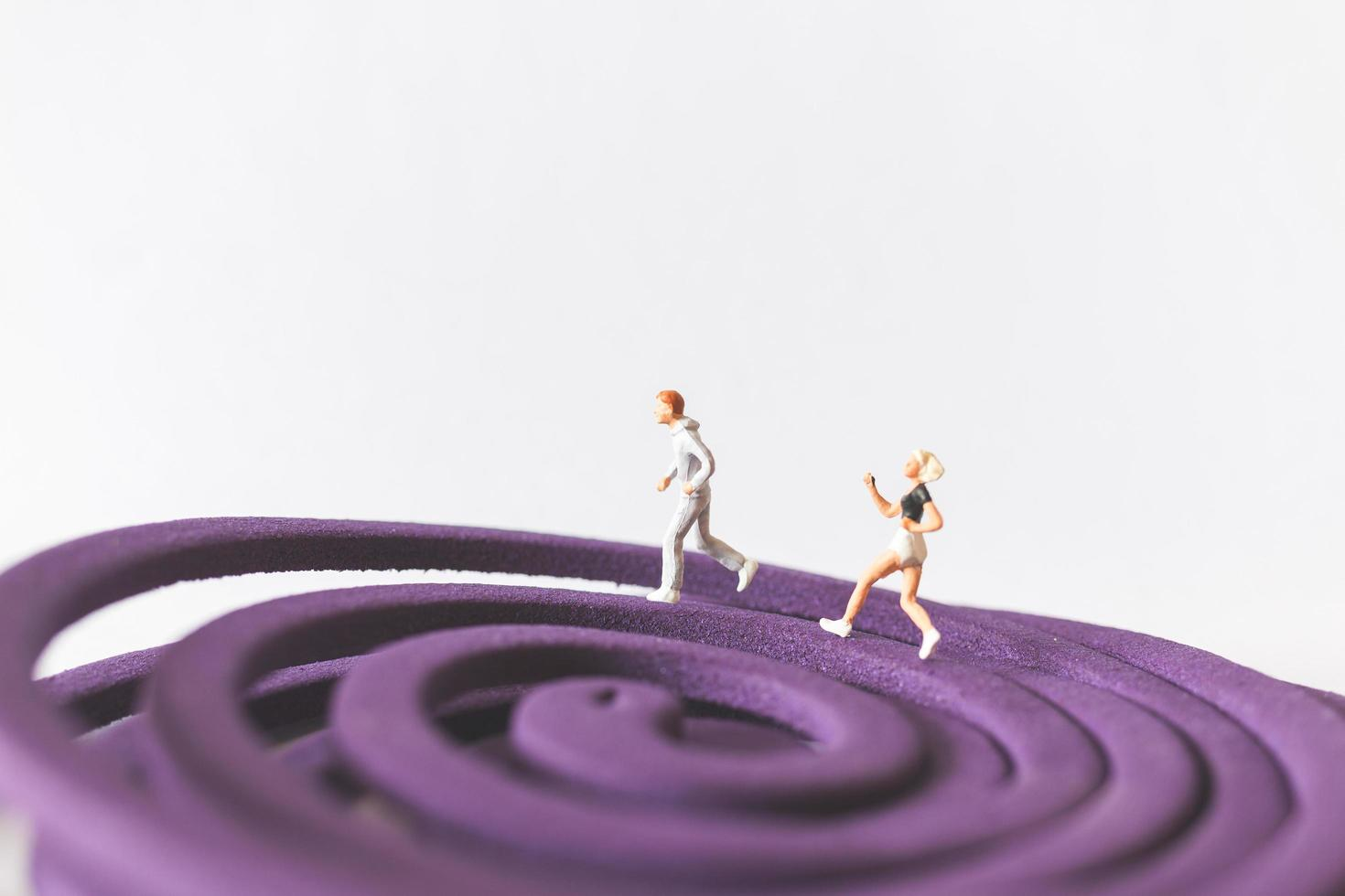 Pareja en miniatura corriendo sobre un campo circular púrpura foto