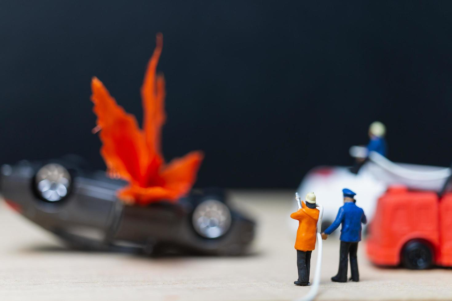 Bomberos en miniatura en un accidente de coche, concepto de accidente de coche foto