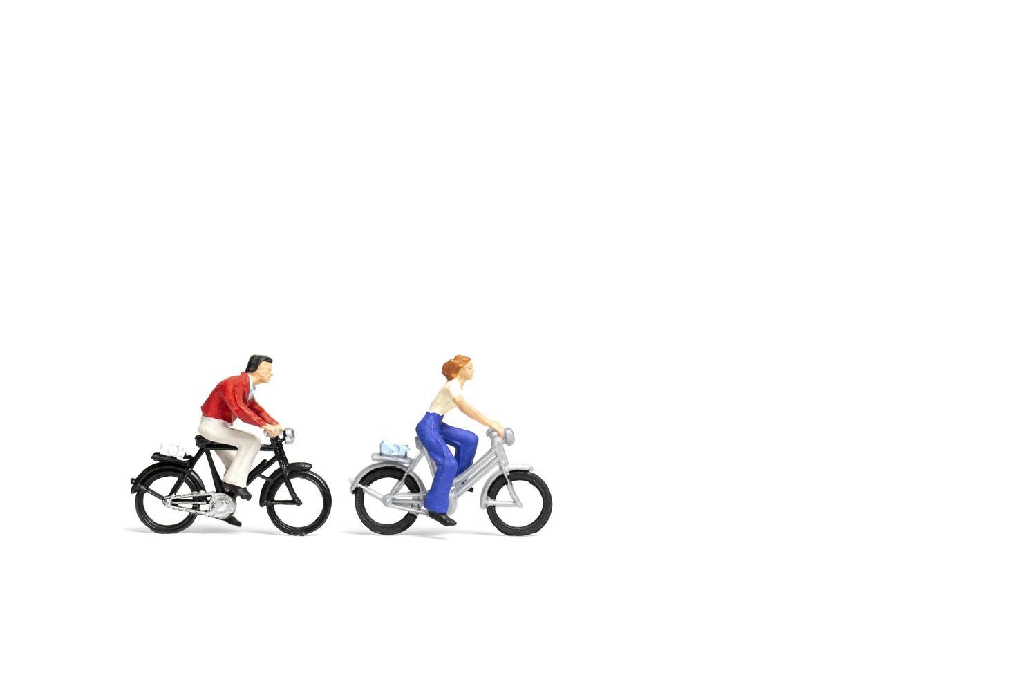 Pareja en miniatura en bicicleta sobre un fondo blanco, el concepto del día de San Valentín foto