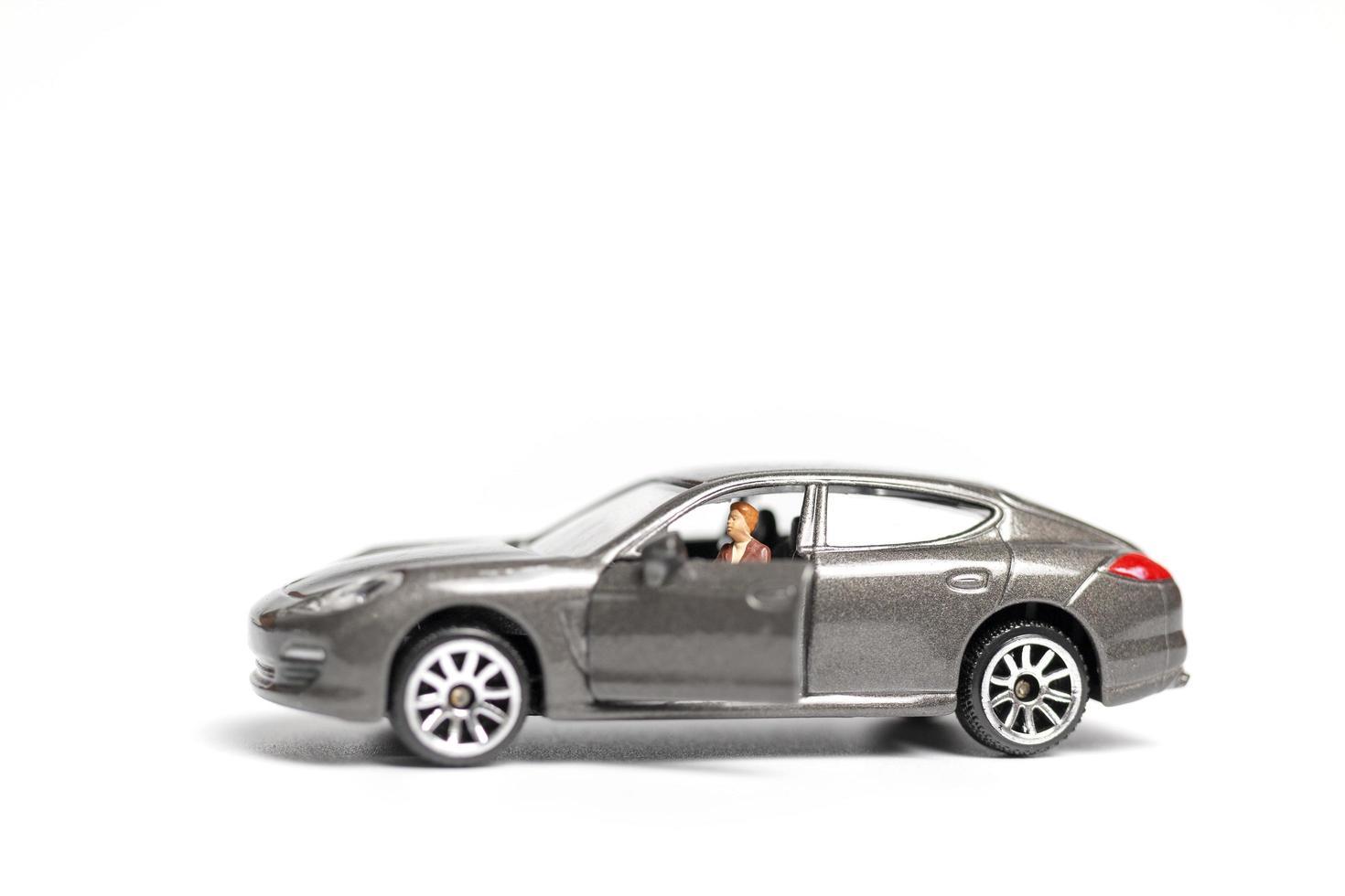 Gente en miniatura sentada en un coche sobre un fondo blanco. foto