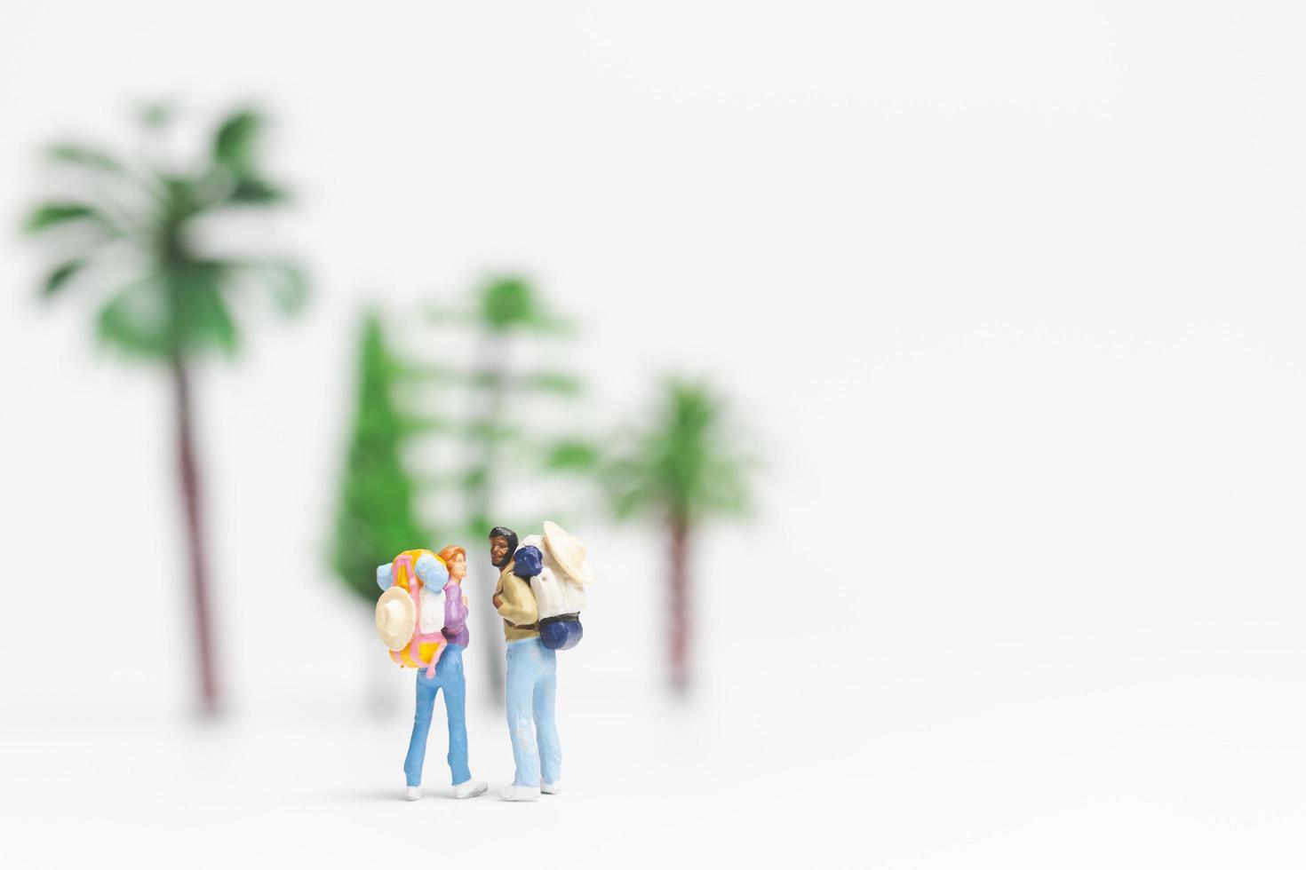 Viajeros en miniatura con mochilas caminando sobre un fondo blanco, concepto de viaje y aventura foto