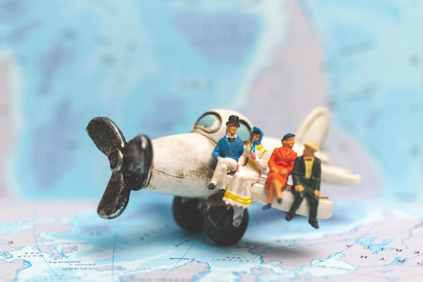Gente en miniatura sentada en un avión con un fondo de mapa del mundo, concepto de viaje foto