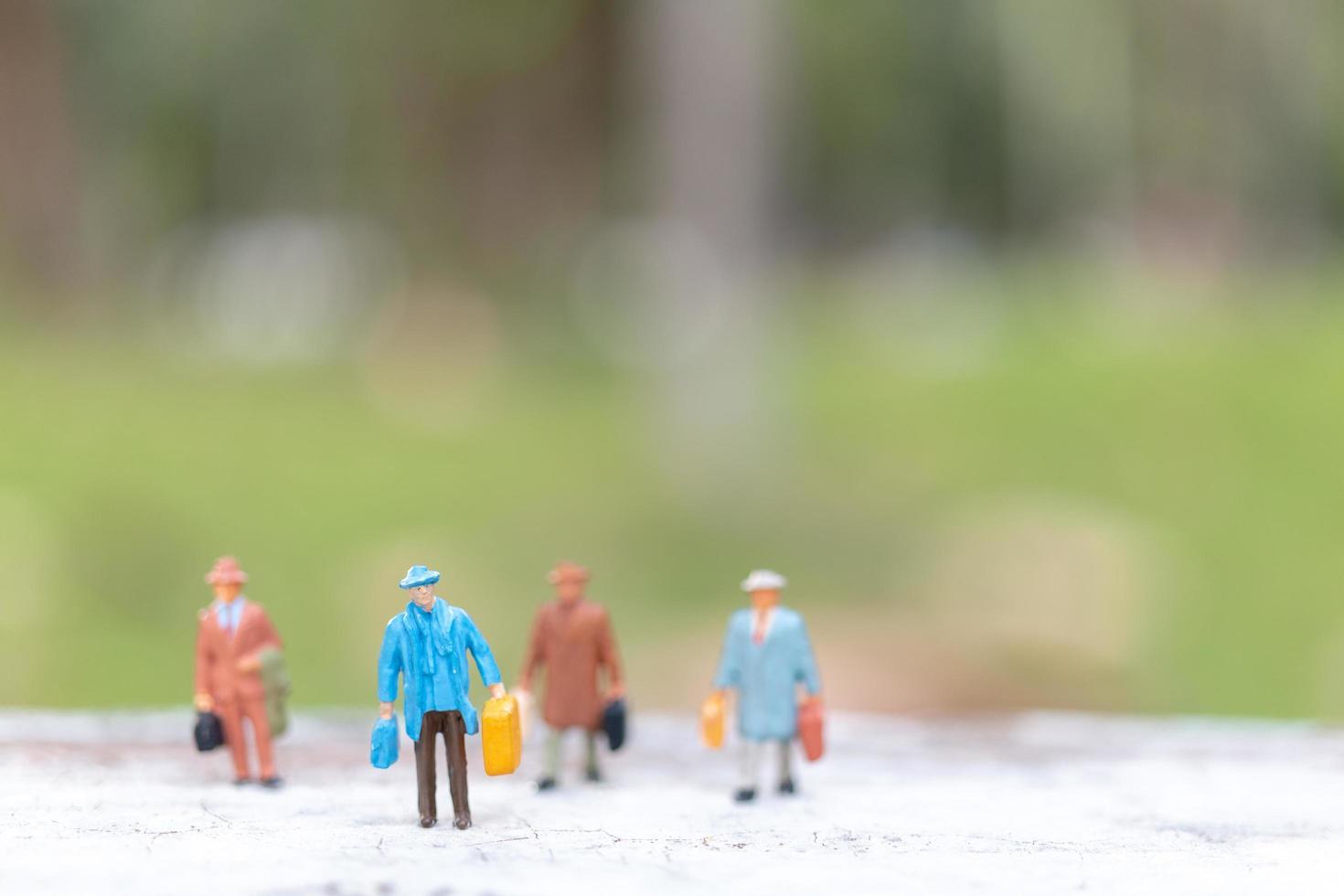 Viajeros en miniatura caminando por una calle, concepto de viaje y aventura. foto