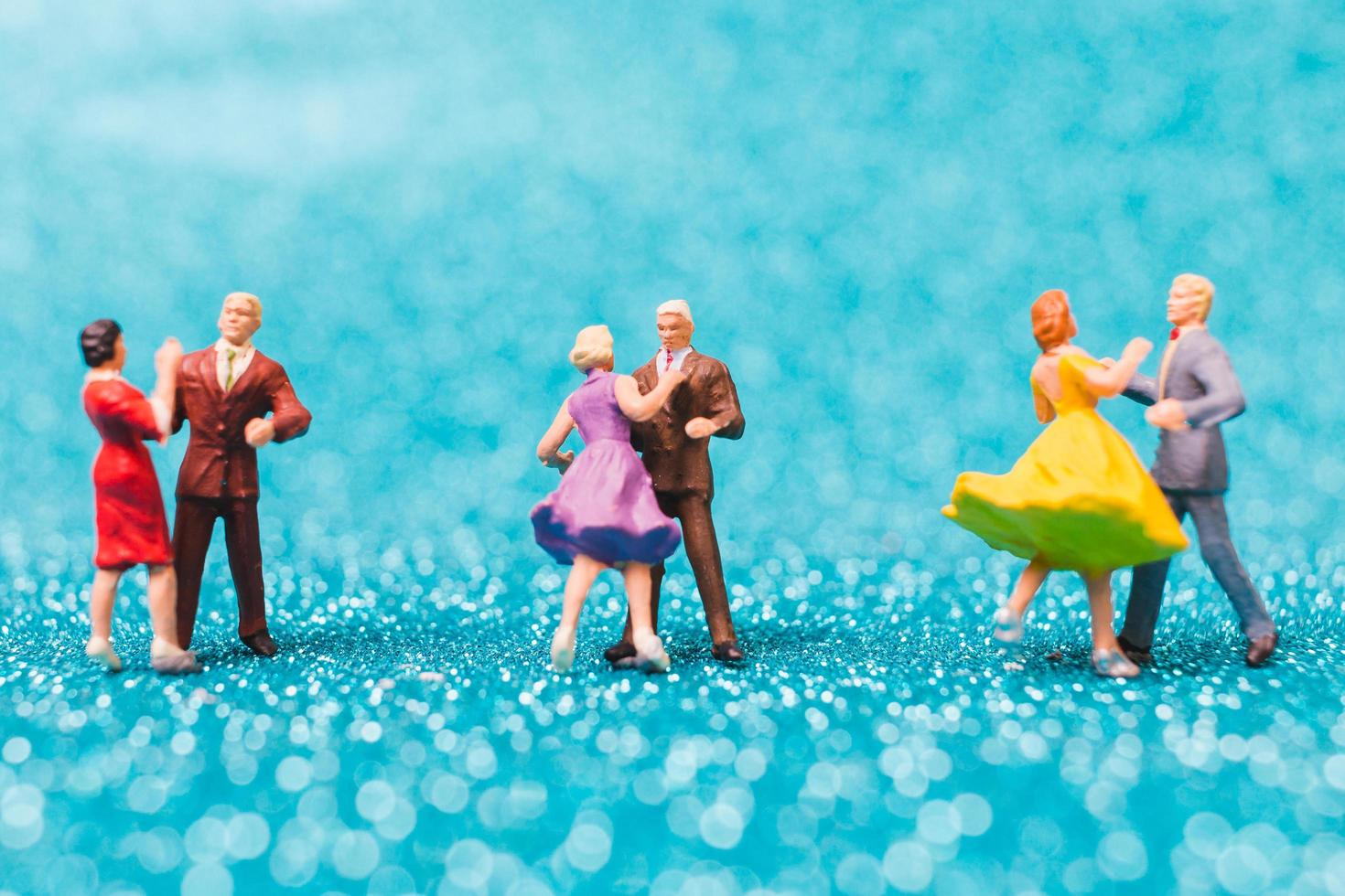 Miniature couples dancing on blue glitter background, Valentine's Day concept photo