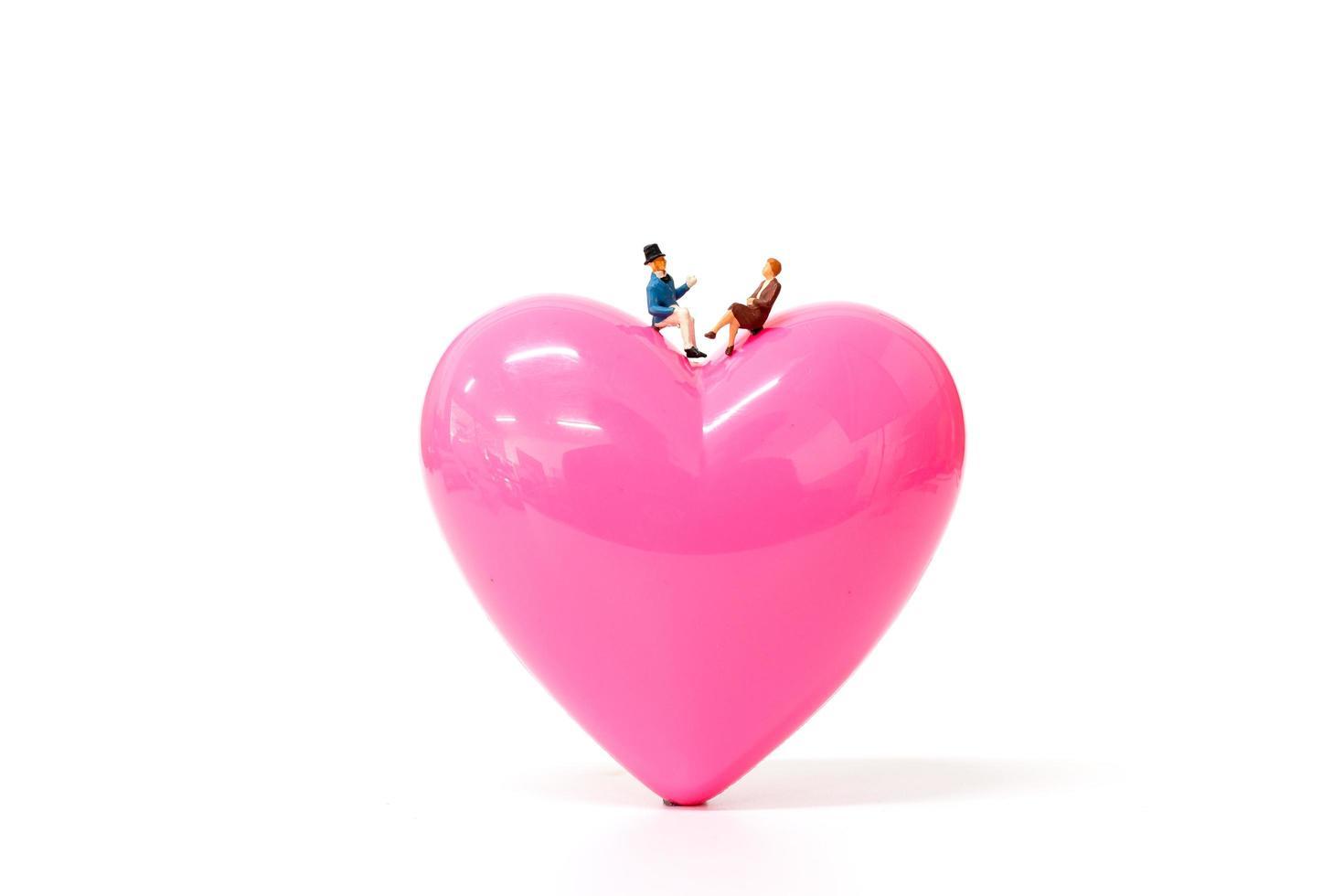 Pareja en miniatura con un corazón de color rosa sobre un fondo blanco, el concepto de San Valentín foto