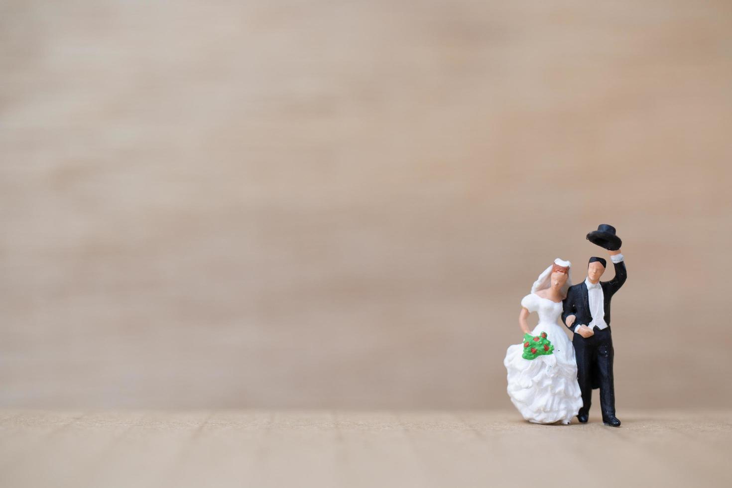 La novia y el novio en miniatura sobre un fondo de madera foto