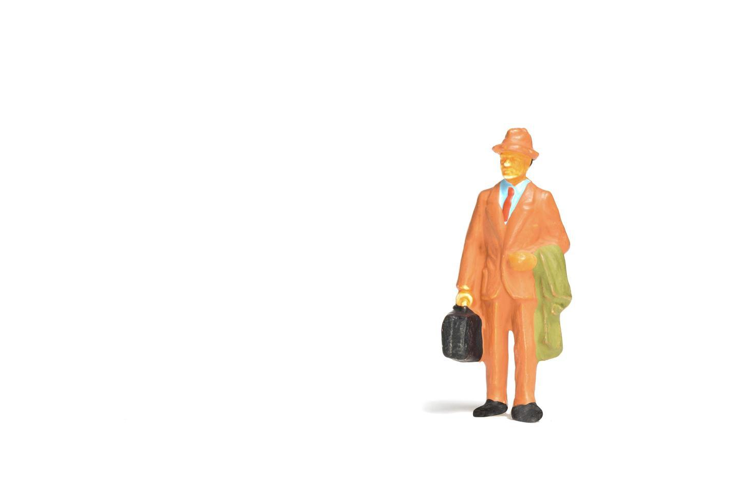 Viajero en miniatura sosteniendo un bolso de pie sobre un fondo blanco, concepto de viaje foto