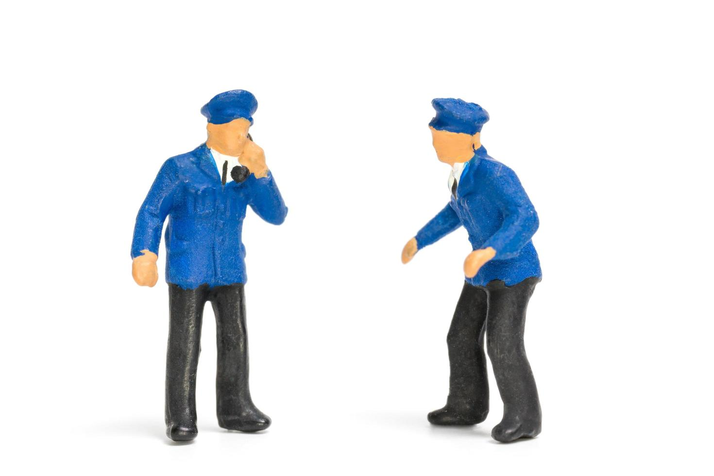 Miniature policemen standing isolated on a white background photo