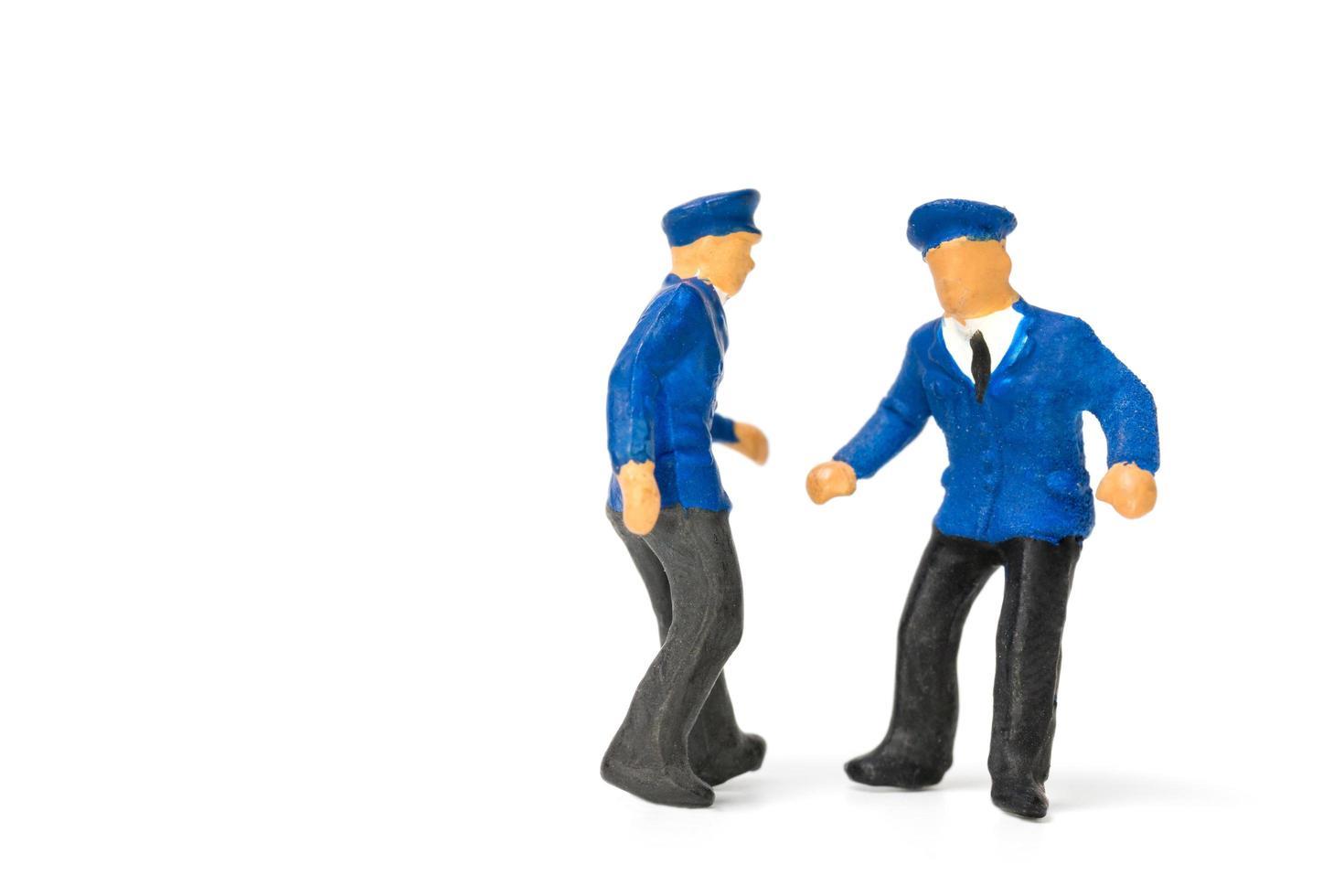 Policías en miniatura que se encuentran aisladas sobre un fondo blanco. foto