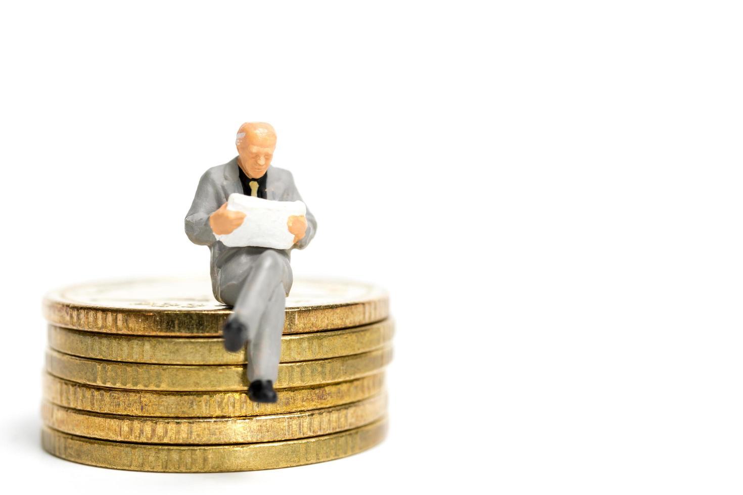 Empresario en miniatura sentado sobre una pila de monedas, dinero y concepto financiero foto