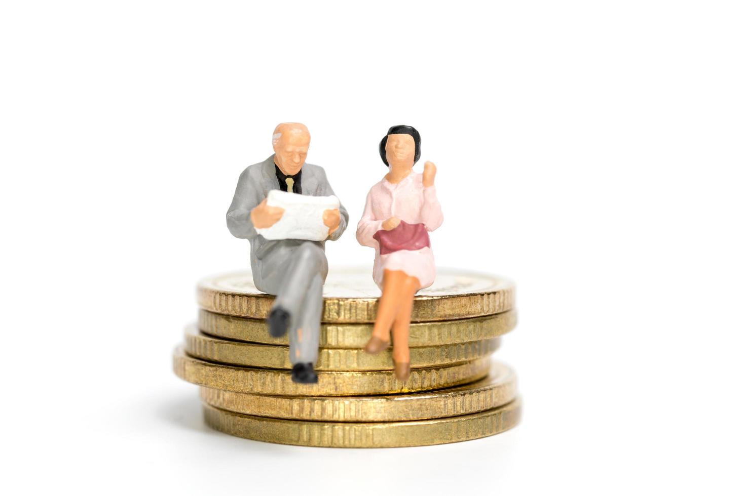 Empresarios en miniatura sentados en una pila de monedas, dinero y concepto financiero foto