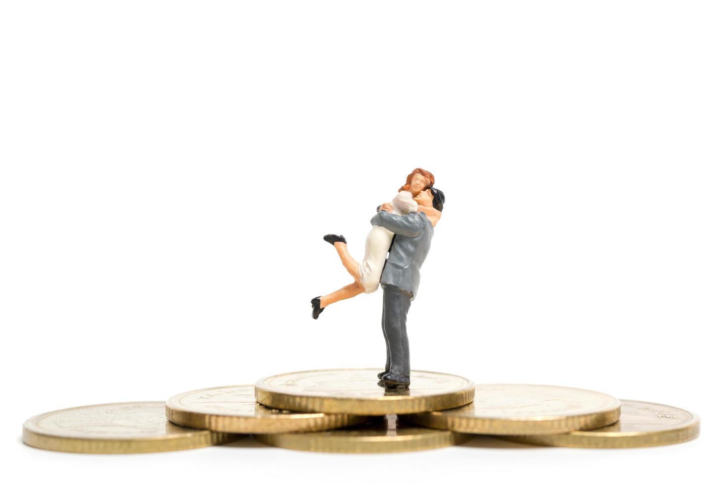 Pareja en miniatura abrazándose en una pila de monedas, dinero y concepto financiero foto
