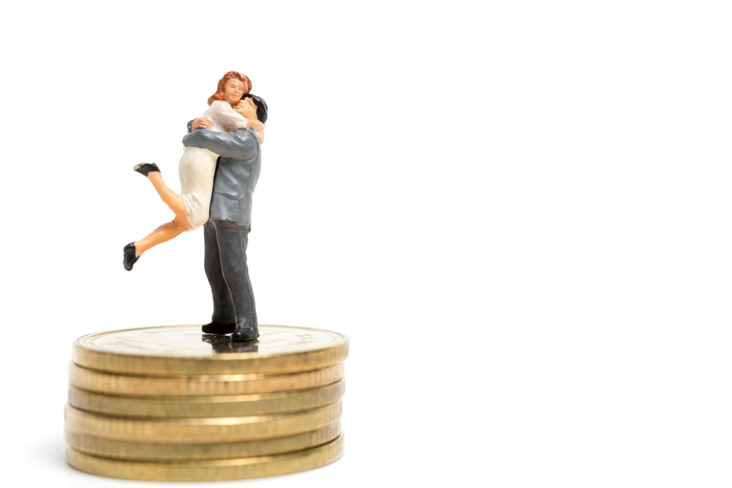 Miniature couple hugging on a stack of coins, money and financial concept photo