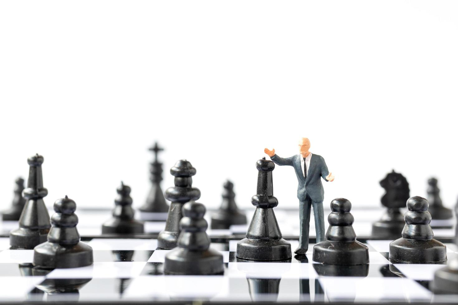 Miniature businessman standing on a chessboard, business and competition concept photo