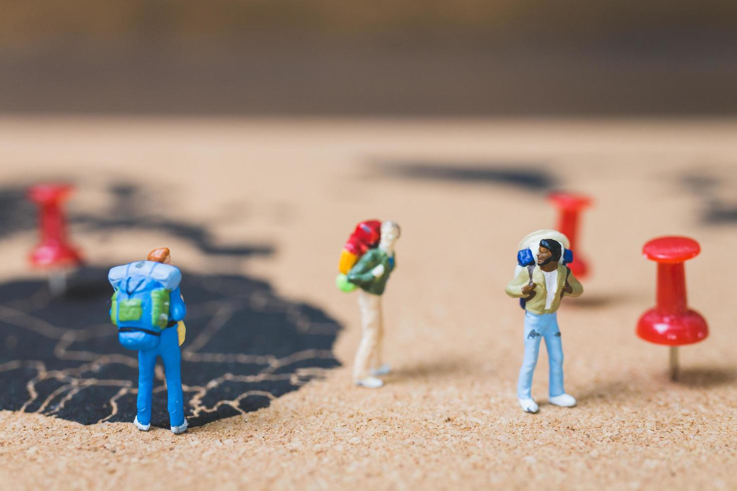 Miniature backpackers walking on a world map, tourism and travel concept photo