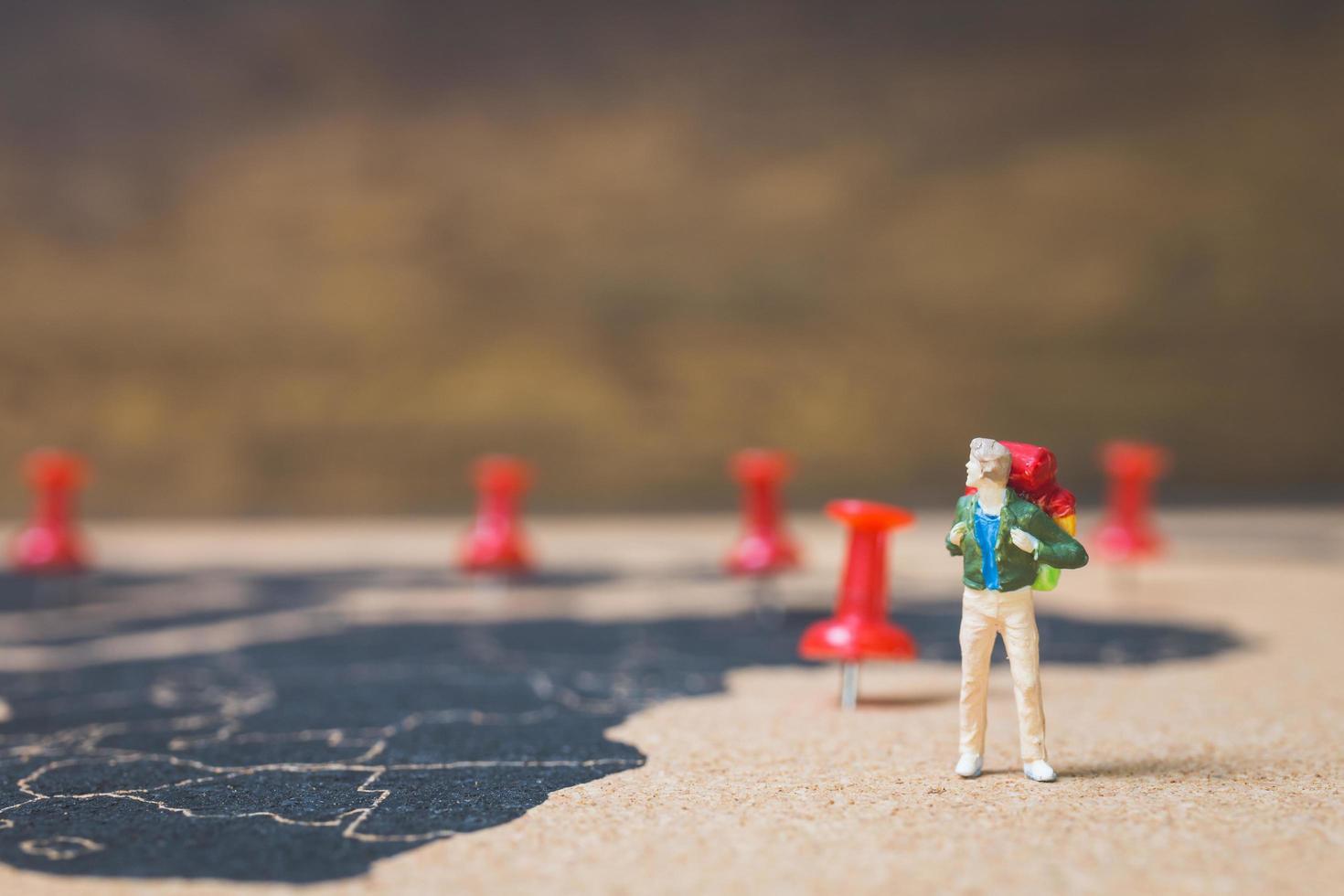 Mochilero en miniatura caminando sobre un mapa del mundo, el turismo y el concepto de viaje foto