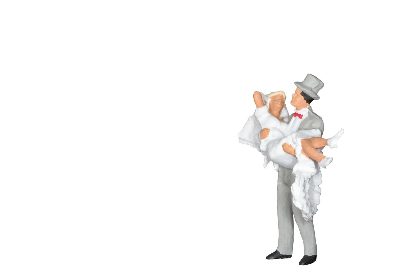 Miniature wedding bride and groom isolated on a white background photo