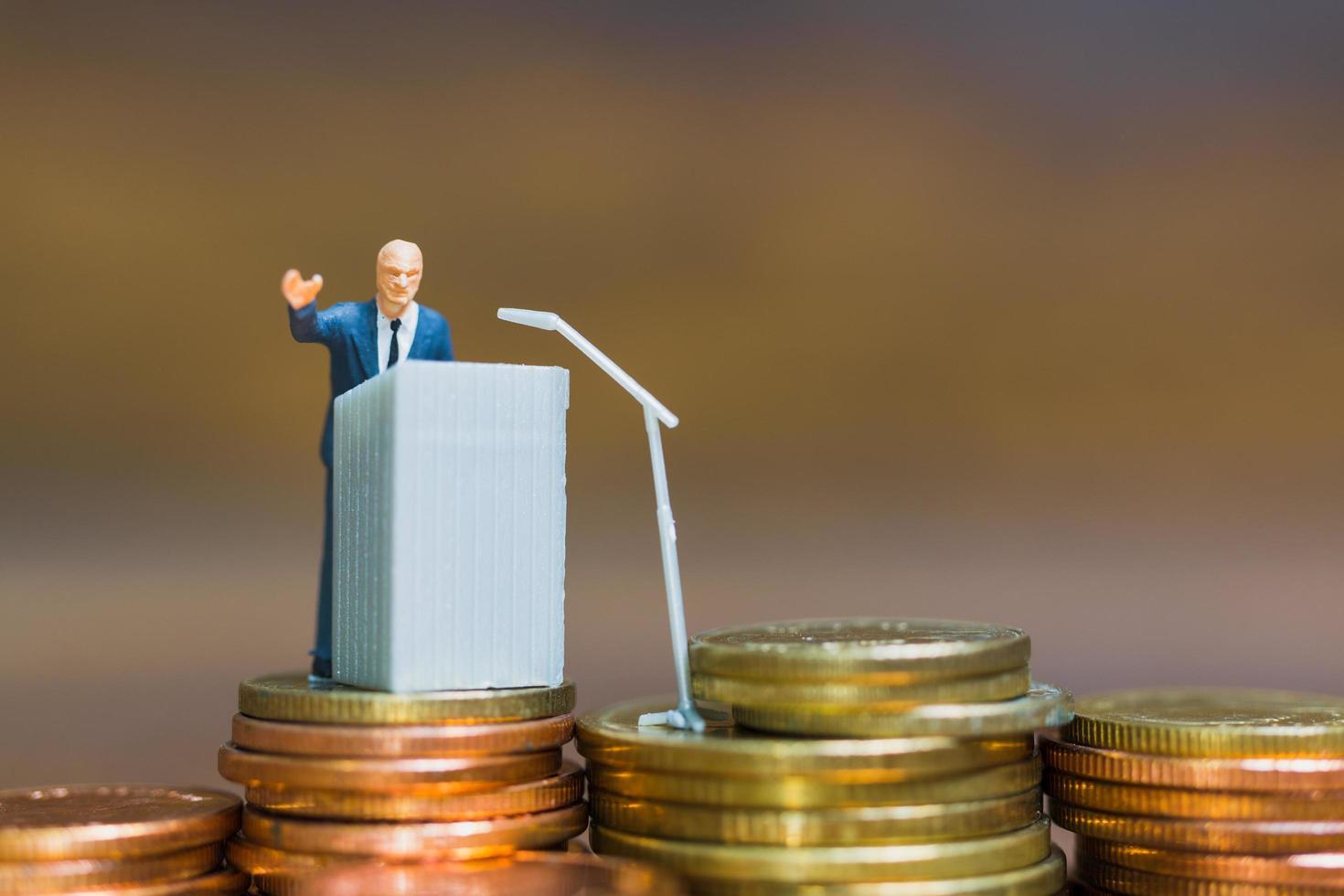 Empresario en miniatura hablando en un podio sobre una pila de monedas, concepto de inversión financiera y empresarial foto
