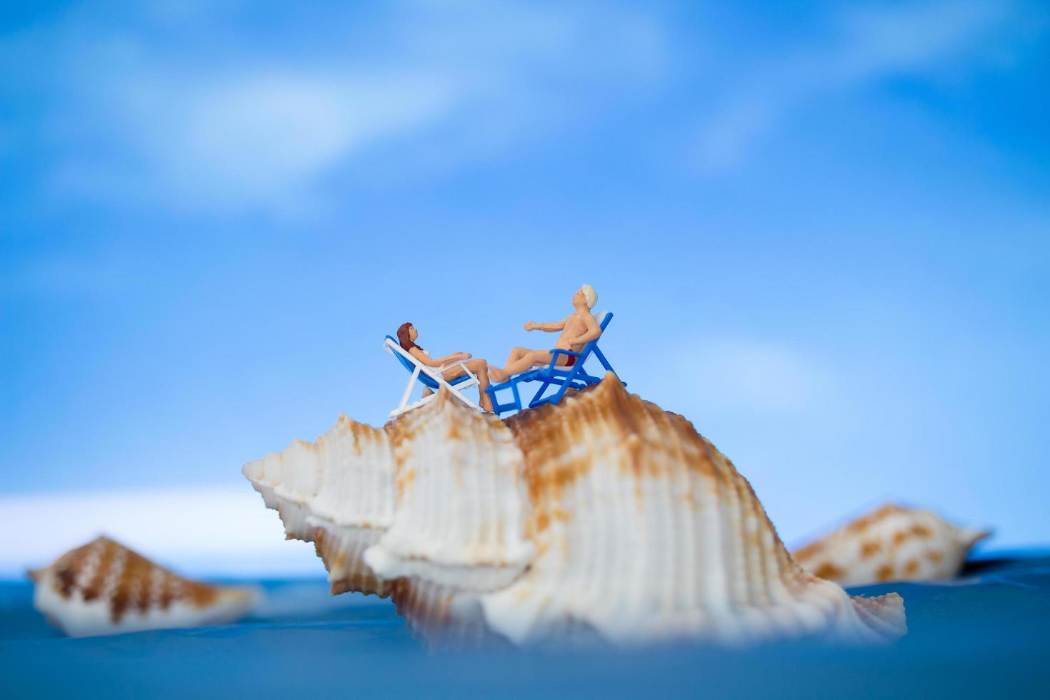 Miniature people sunbathing on a seashell with a blue sky background, summer vacation concept photo