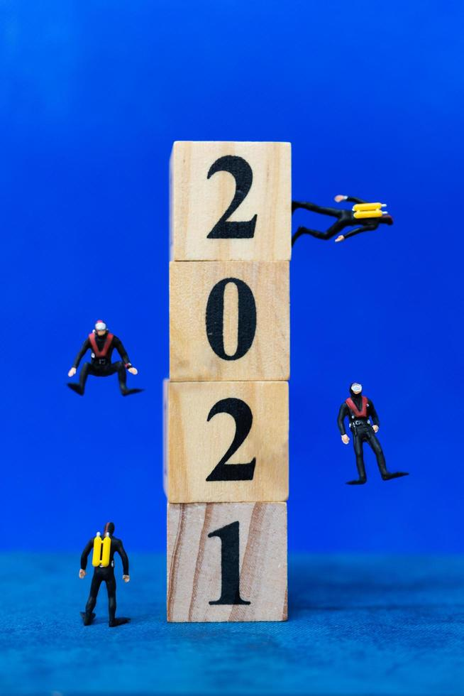 Miniature divers diving around wooden blocks with the number 2021, Happy New Year concept photo