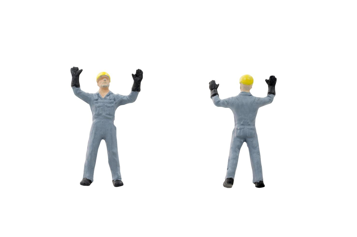 Miniature construction workers on a white background photo