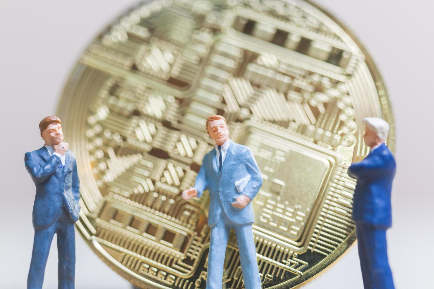 Miniature businessmen standing in front of a Bitcoin cryptocurrency coin, business concept photo