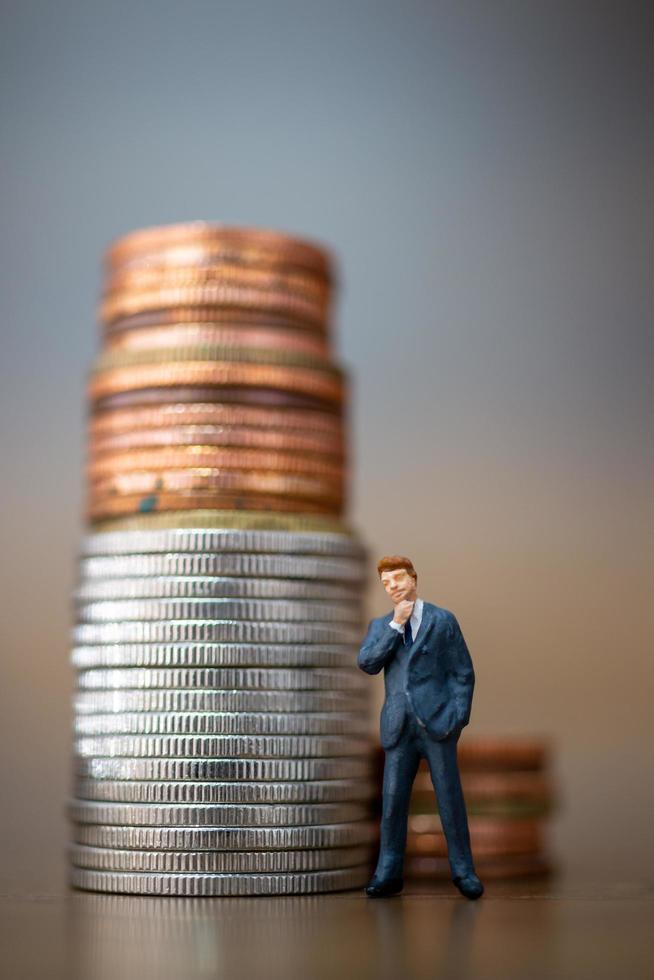 Empresario en miniatura de pie con una pila de monedas, concepto de crecimiento empresarial foto
