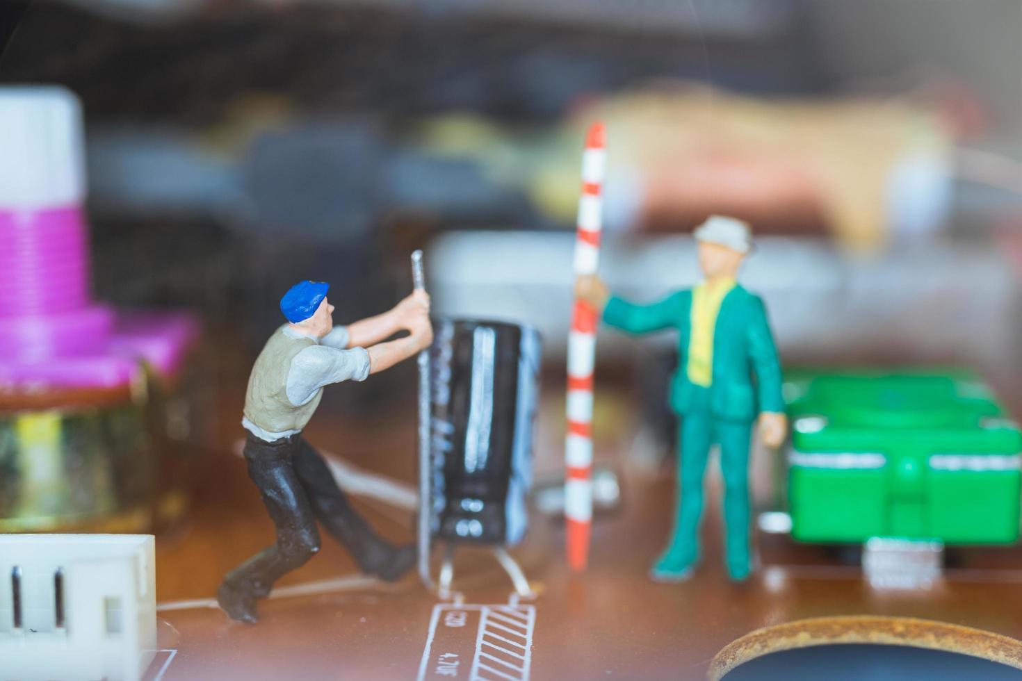 Trabajadores en miniatura que se unen para reparar circuitos electrónicos, concepto de trabajadores de la construcción foto