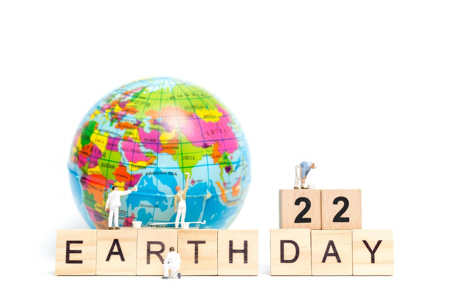 Pintores en miniatura pintando en un globo terráqueo con bloques de madera que muestran el día 22 de la tierra sobre un fondo blanco, concepto del día de la tierra foto