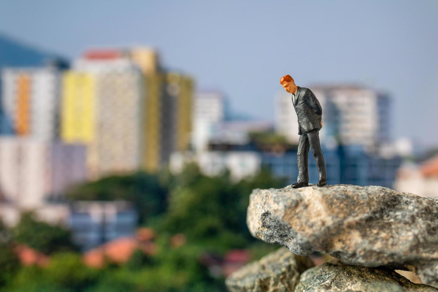 Miniature businessman standing on a rock with buildings in the background photo